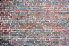 Grijs rood patroon, textuur, bakstenen muur met verschillende gekleurde bakstenen, rood, groen, grijs, bruin in de zomer royalty-vrije stock afbeelding