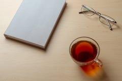 Grijze agenda, kop thee, en glazen op een bruine lijst, selectieve nadruk royalty-vrije stock foto