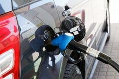 Grijze auto bij benzinestation die met brandstof worden gevuld royalty-vrije stock foto's