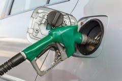 Grijze auto bij benzinestation die met brandstof worden gevuld Stock Foto