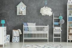 Grijze babyslaapkamer met wieg royalty-vrije stock foto