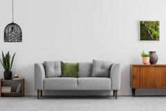 Grijze bank met hoofdkussens naast houten kast in woonkamerbinnenland met lamp en affiche Echte foto stock foto's