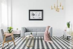 Grijze bank met roze deken in het kader van affiche in wit vlak binnenland met leunstoel en gouden lijst Echte foto royalty-vrije stock afbeelding