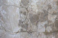 Grijze concrete muur als achtergrond met barsten met exemplaarruimte stock foto's