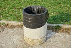 Grijze concrete urn met een zwarte plastic zak op de stoep dichtbij het groene gazon Royalty-vrije Stock Afbeeldingen