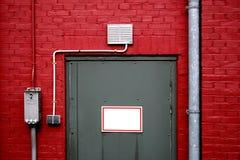 Grijze deur op rode muur Royalty-vrije Stock Foto
