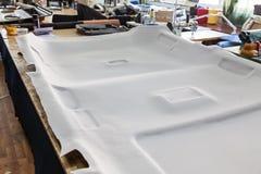 Grijze die plafondbekleding uit de auto voor het stemmen en het vastbinden met grijs zacht materiaal op een lijst in de workshop  royalty-vrije stock foto