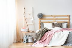 Grijze die pompom op houten bedhead door kingsize bed met spatie wordt geplaatst stock foto