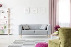 Grijze die zitkamer met hoofdkussens in echte foto van wit woonkamerbinnenland worden geplaatst met affiches op muur, vuil roze g royalty-vrije stock fotografie
