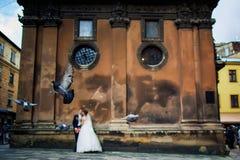 Grijze duiven tijdens de vlucht, in het achtergrondhuwelijkspaar in liefde bij oude kerk Stock Foto