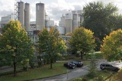 Grijze fabriek met groen bomen en parkeren stock foto's