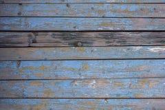 Grijze gele oude omheiningsmuur van houten planken met blauwe schilverf en barsten en één donkere raad Horizontale lijnen Ruwe op royalty-vrije stock afbeeldingen