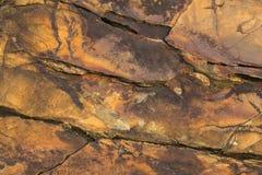 Grijze gele rode zwarte rots met diepe hulp, barsten en schaduwen natuurlijke oppervlaktetextuur stock afbeeldingen