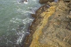 Grijze gele rots met overzeese eikels in het overzees royalty-vrije stock afbeeldingen