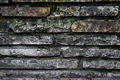 Grijze granietmuur, roodachtige stenen, cement en moos stock fotografie