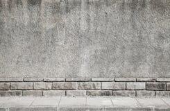 Grijze grungy concrete muur en betegelde weg Stock Fotografie