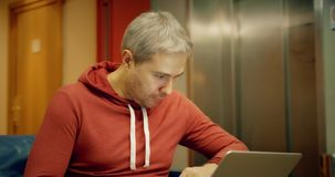 Grijze haired Kaukasische mens in vrijetijdskleding die zijn laptop in de hotelgang met behulp van stock videobeelden