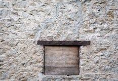 Grijze hand gebouwde steenmuur met venster en mantel Stock Foto