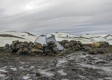 Grijze het kamperen tent in Hrafntinnusker-kampeerterrein in slechte weersomstandigheden, Laugavegur-stijging, Fjallabak-Natuurre stock foto
