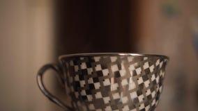 Grijze kop op de lijst Giet kokend water van de ketel Zijaanzicht, mening van een paar van een mok stock videobeelden