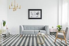 Grijze laag en leunstoel op geruite vloer in wit vlak binnenland met gouden lamp en affiche Echte foto stock foto