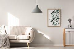 Grijze lamp in helder woonkamerbinnenland met affiche naast bei royalty-vrije stock foto