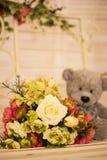 Grijze leuke teddybeerzitting op schommeling met bloemen voor ogenblik van liefdeconcept Stock Afbeelding