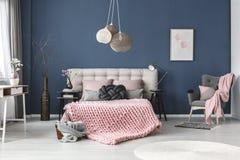Grijze leunstoel met roze deken stock foto's