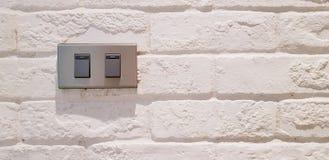 Grijze lichte die schakelaarknoop op witte ruwe of uitstekende muur wordt geïnstalleerd royalty-vrije stock foto's