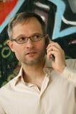 Grijze mens op telefoon Stock Foto