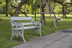 Grijze metaalbank in het park stock fotografie