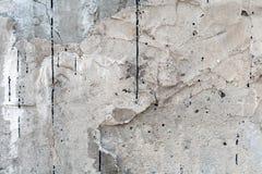 Grijze muur die met een ongelijke ruwe laag van pleister met gaten, onregelmatigheden, barsten en dun sporen van stromende zwarte stock foto's