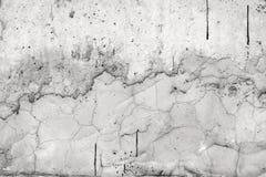 Grijze muur die met een ongelijke ruwe laag van pleister met gaten, onregelmatigheden, barsten en dun sporen van stromende zwarte stock foto