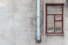 Grijze muur met glanzende pijp Stock Foto