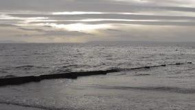 Grijze oceaangolven die tegen kust onder een gedeeltelijk donkere middaghemel omwikkelen stock footage