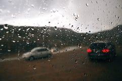 Grijze regendruppels op het autoraam op een bewolkte dag Buiten het venster van de autosilhouetten van het overgaan van auto's royalty-vrije stock fotografie