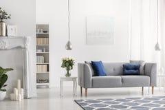 Grijze sofa met blauwe kussens in wit elegant woonkamerbinnenland met bloemen en het schilderen Echte foto royalty-vrije stock fotografie
