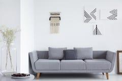 Grijze sofa met hoofdkussens in wit woonkamerbinnenland met affiches en installatie op lijst Echte foto stock foto's