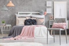Grijze stoel met roze hoofdkussen stock fotografie