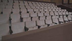 Grijze stoelen in een lege bioskoopzaal Lege stoelen De mislukking van de film op het bespreekbureau stock video