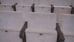 Grijze stoelen in een lege bioskoopzaal Lege stoelen De mislukking van de film op het bespreekbureau stock footage