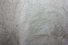 Grijze textuur met gekrast pleister op de muur, stock afbeelding