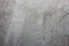 Grijze textuur met gekrast pleister op de muur, stock fotografie