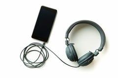 Grijze uitstekende hoofdtelefoons en cellphone royalty-vrije stock fotografie