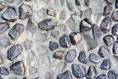 Grijze verpletterde stenen op de muur van cement en drukken van uitgevallen royalty-vrije stock fotografie