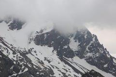 Grijze wolken van de bergen de witte sneeuw stock afbeelding