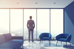 Grijze woonkamer, blauwe bank, zolder, zakenman Stock Afbeelding