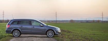 Grijze zilveren lege die auto over grint landelijke weg wordt geparkeerd op vage groene weiden, verre stadsgebouwen en de duideli royalty-vrije stock fotografie