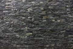 Grijze zwarte steentextuur van de bakstenen muur van een privé huis Stock Foto's