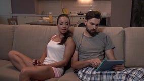 Gril紧接坐有她的丈夫的沙发 她在手上有电话,他拿着片剂 看什么的妇女开始 股票录像
